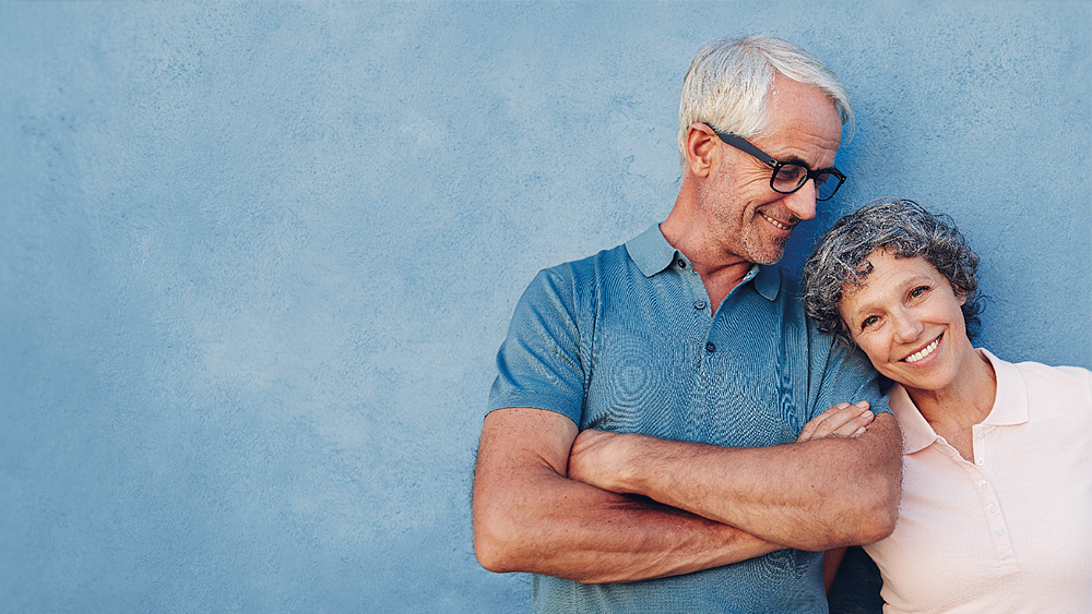 Wellspect Lofric Happy husband and wife in front of a blue background